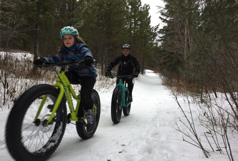 Girl and man riding fat bikes in the snow