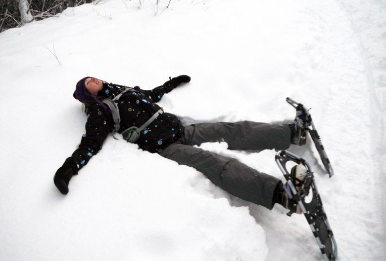 woman lying in snow with snowshoes