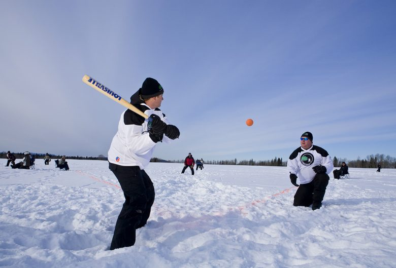 two men playing softball in snow