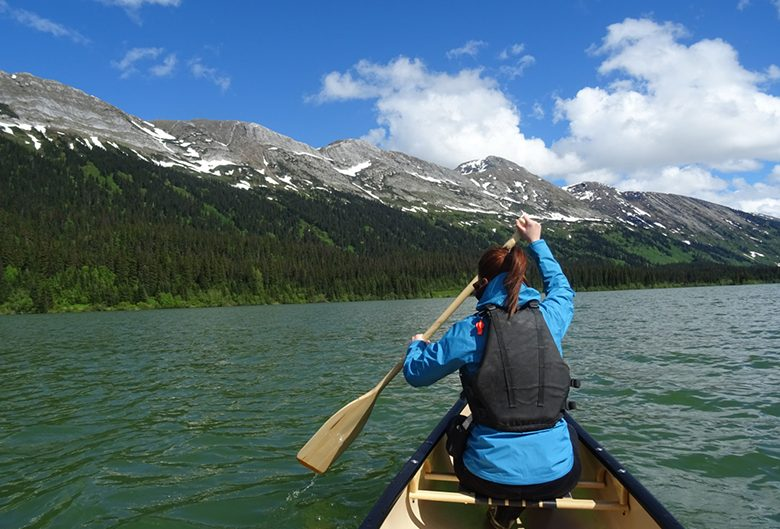 woman canoe lake mountains