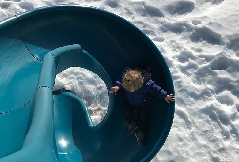 kid on a slide in winter