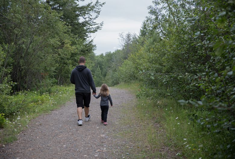man and girl walking on trail