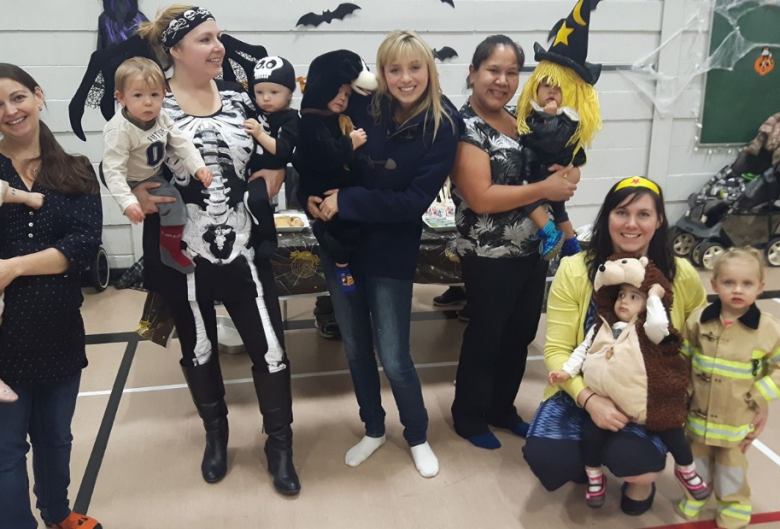 women and kids in Halloween costumes