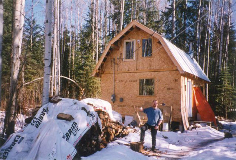man in front of cabin