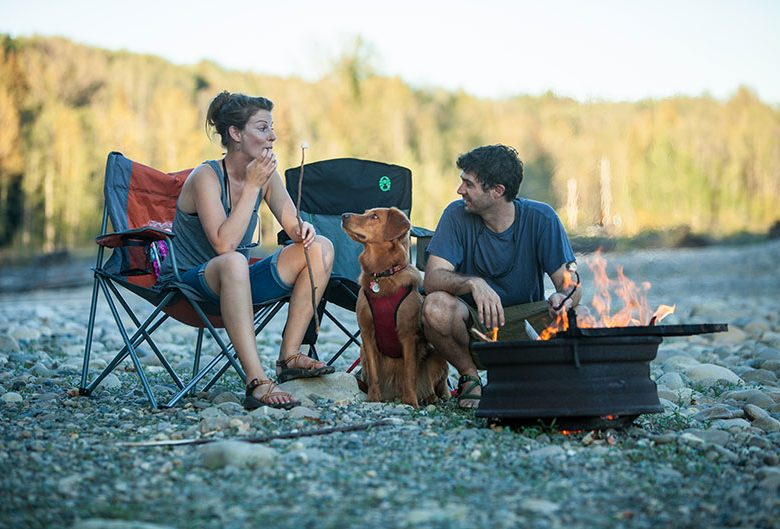 two people dog campfire