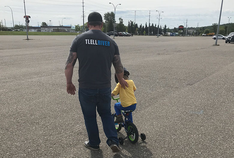 Dad teaching son how to ride a bike.