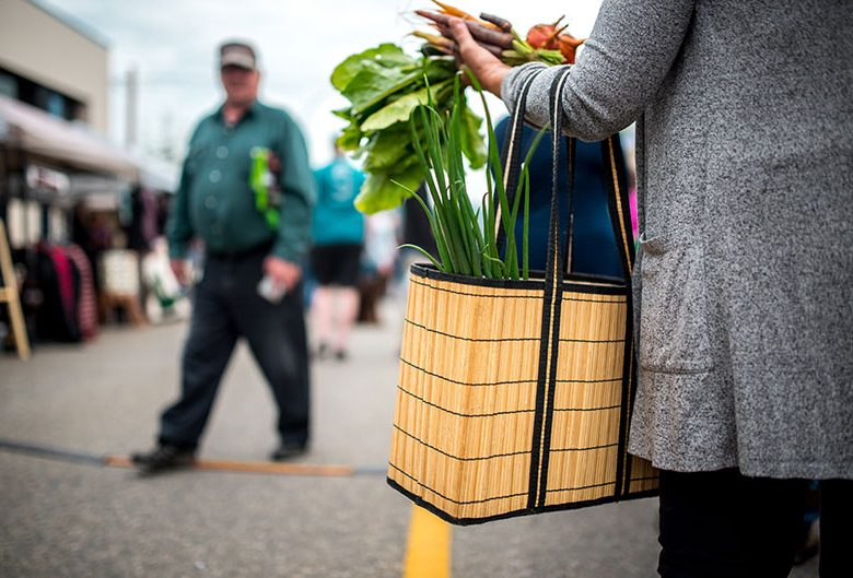 Woman holding bag of vegetables at Farmers' Market.