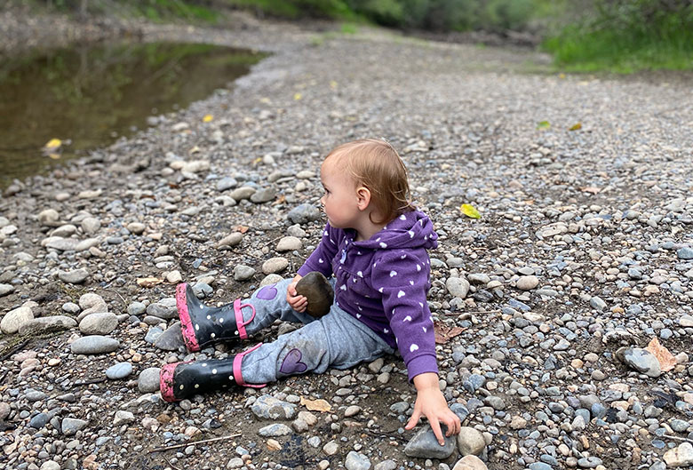 Girl picking up rocks.