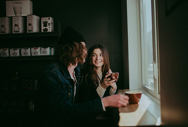 Man and woman drinking coffee by a window.