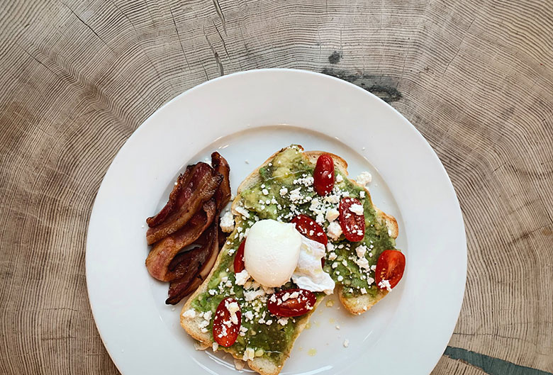 Avocado and poached egg on toast with bacon.