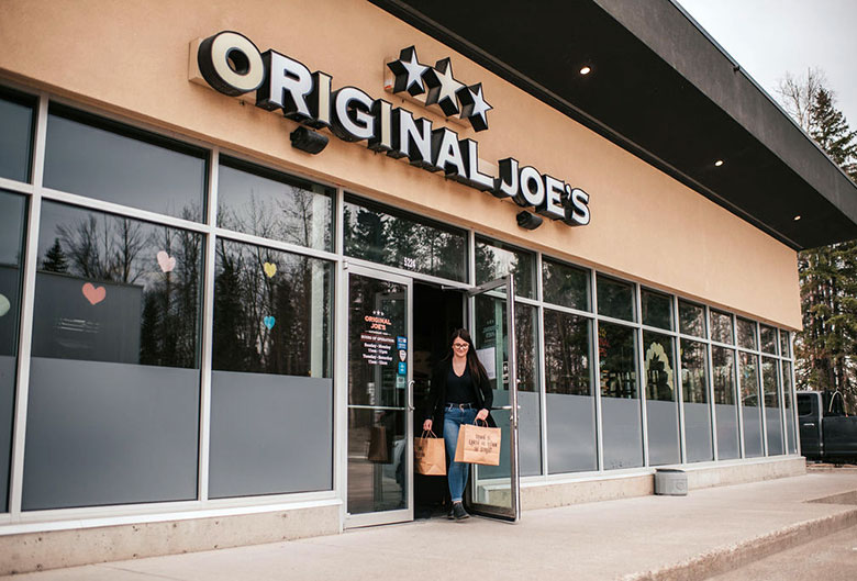 Woman leaving Original Joe's with take out food.