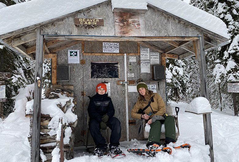 Woman and her son in front of snow covered cabin