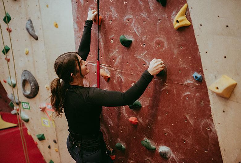 Woman climbing wall at climbing gym.