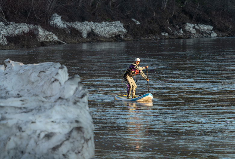 Woman paddle boarding down river.