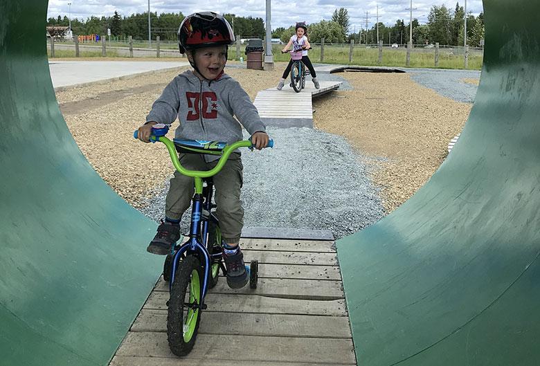 Kids riding bikes at park.