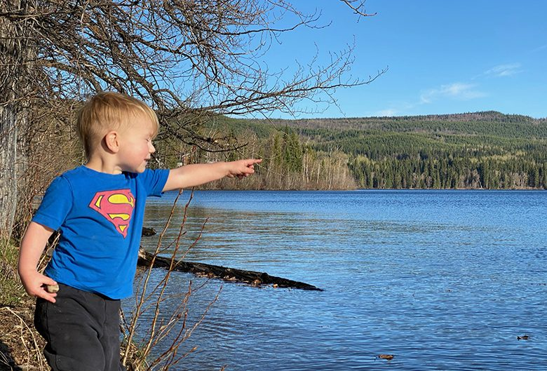 Boy in Superman shirt pointing to shore at the lake in summer