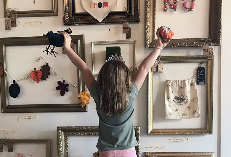 Girl in front of craft wall.
